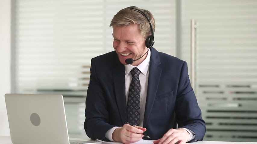 Businessman sitting at desk in office wearing headset using microphone talks negotiating with company client makes notes, videoconferencing make deal solve business issues online via internet concept
