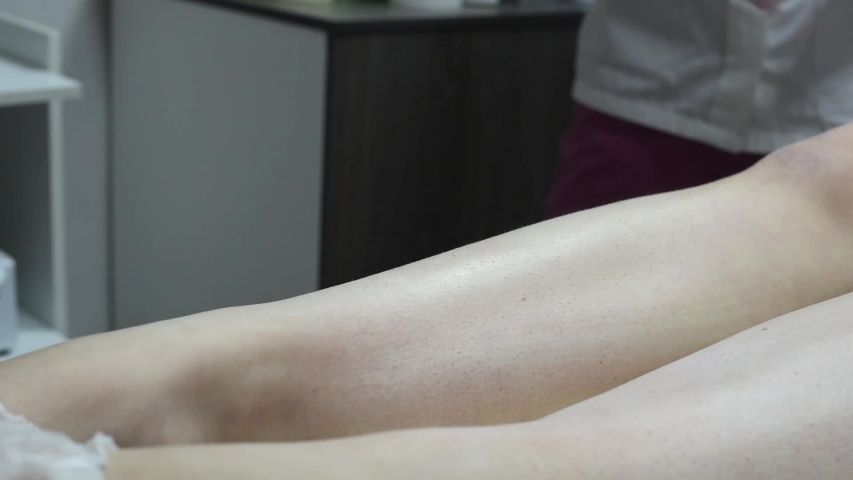 Close-up of one of the stages of the procedure for removing hair on the legs of a woman by waxing | Shutterstock HD Video #1039796762