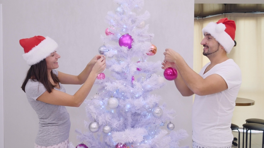 Funny wife and husband standing on different sides of silver christmas tree, fooling around and decorating, dressed in nice santa hats. | Shutterstock HD Video #1039815758