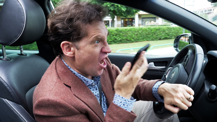 Angry man screaming on phone while driving car #1039833842