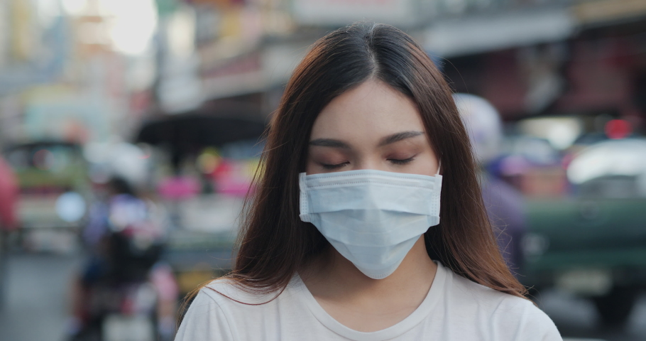 Woman wearing mask and looking to camera at city. Health care and medical concept. | Shutterstock HD Video #1039834265
