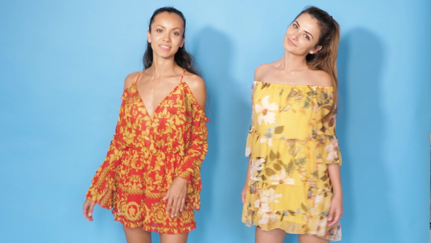 Two young beautiful smiling hipster girls in trendy summer clothes.Sexy carefree women posing in studio near blue wall.Positive models dancing.They spinning around and shaking their dresses