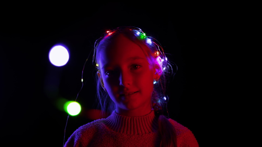 Content girl talking and playing with Christmas garland wreath flashing. Adorable teenage girl with illuminated colorful xmas garland on hand smiling at camera in darkness | Shutterstock HD Video #1039861373