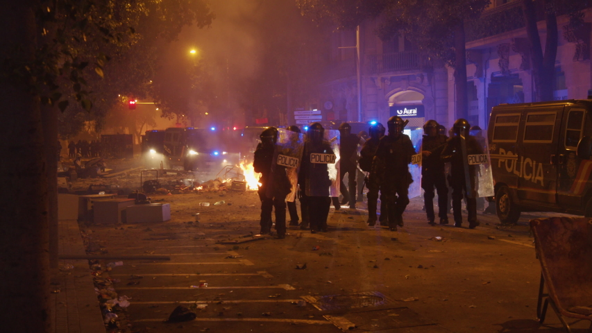 BARCELONA, SPAIN – OCTOBER 18, 2019: Riot police walk past fires and vandalism on Via Laietana in Barcelona, Spain during massive protests in October 2019. ProRes file, shot in 4K UHD.