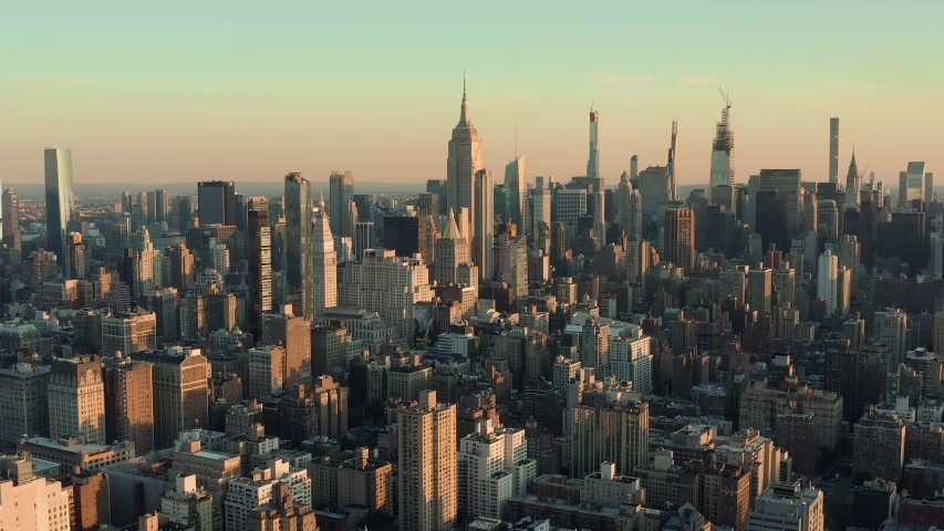 Flying backwards above Manhattan buildings, New York City at sunrise Royalty-Free Stock Footage #1039883120