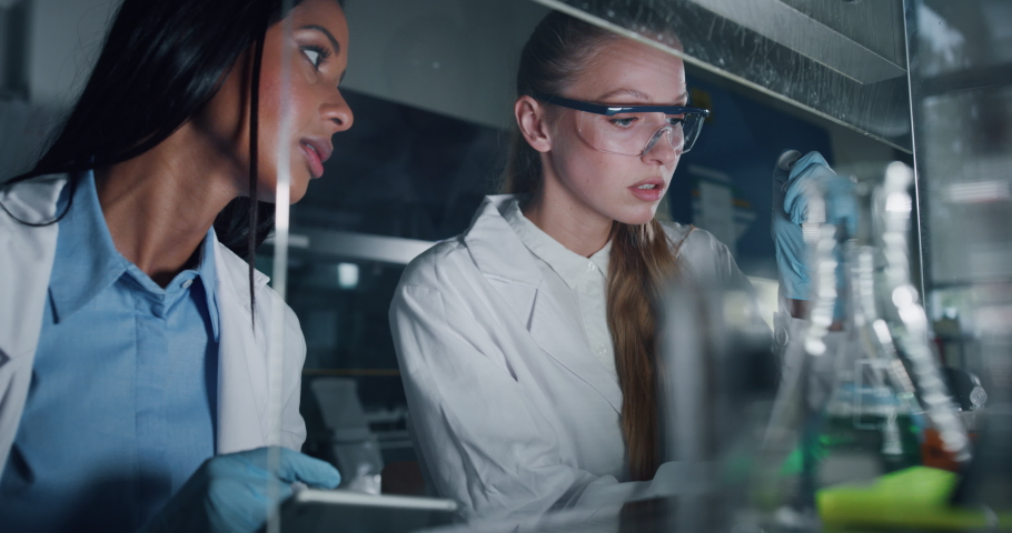 Portrait of two female scientists are analyzing with a pipette a liquid to extract the DNA and molecules in the test tubes in laboratory.  Royalty-Free Stock Footage #1039894493