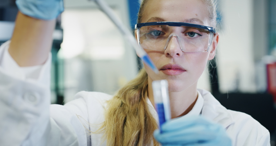 Portrait of blond female scientist is analyzing with a pipette a liquid to extract the DNA and molecules in the test tubes in laboratory.