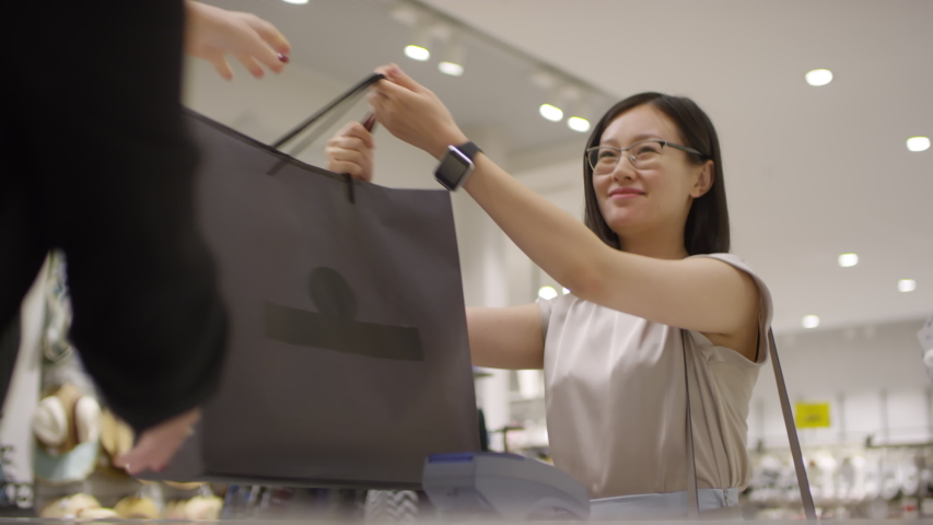 Waist-up shot of smiling Asian woman scanning her palm on payment terminal at checkout counter of clothing store, taking shopping bags from sales assistant, thanking, saying goodbye and leaving Royalty-Free Stock Footage #1039895603