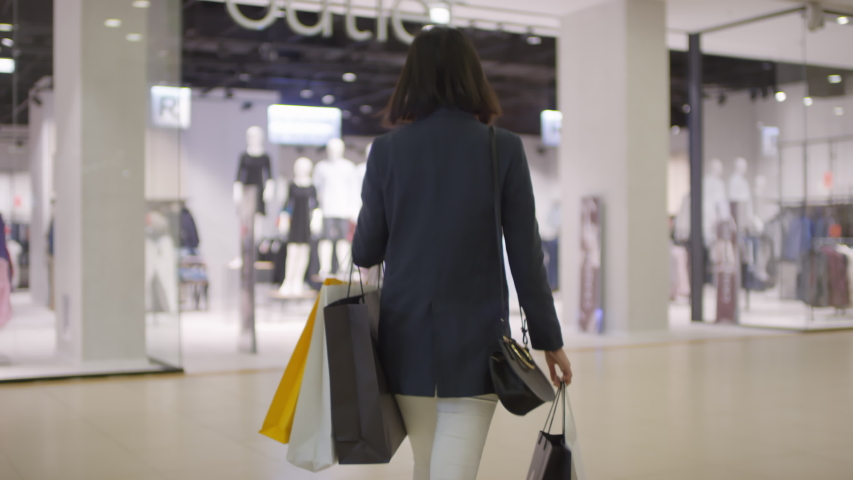 Tracking rear shot of slim young woman in white jeans and blazer with plenty of shopping bags walking through mall and entering brightly lit clothing chain store with mannequins on display Royalty-Free Stock Footage #1039896245