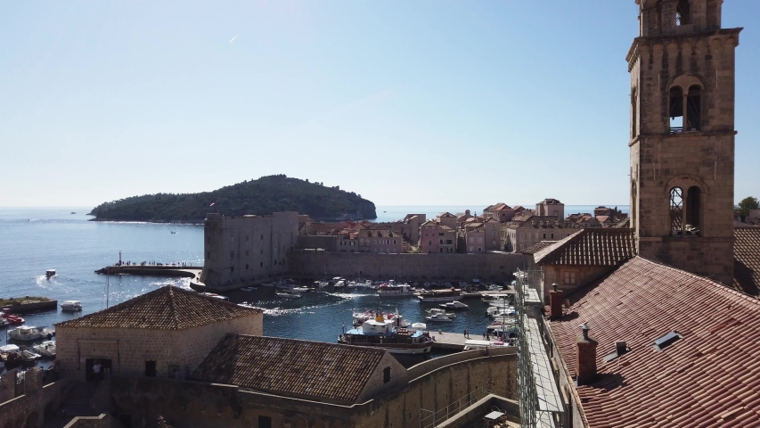 Dubrovnik, Croatia - October, 2019: Unique aerial view from above the port of the walled ancient city of Dubrovnik. Boats are seen coming and going in the port. Tourists are walking on the wall.     Shutterstock HD Video #1039909283