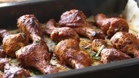 Roasted chicken legs BBQ in baking pan decorating with sesame and herbs. Video shot 4K 50 fps.