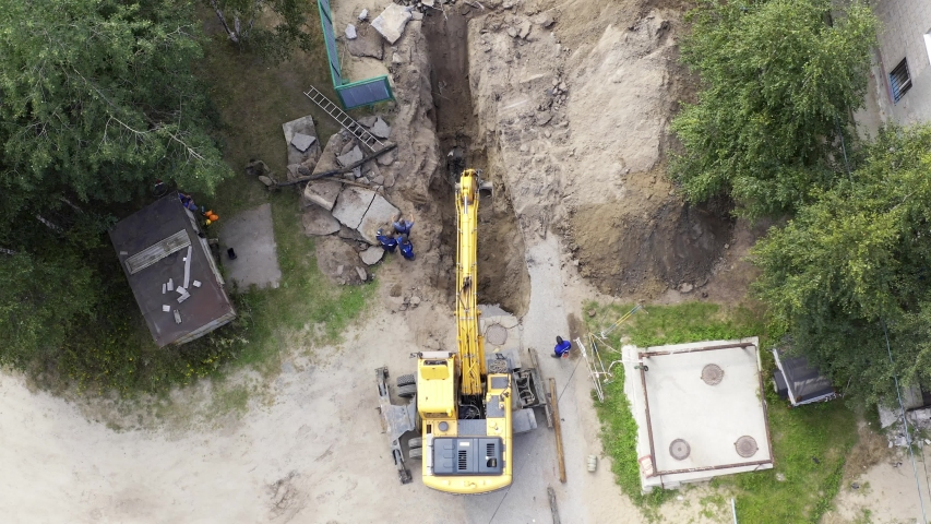 Yellow excavator and workers digging a hole for laying pipes in the summer next to a residential building. Aerial view. #1039922306