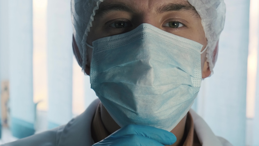 Portrait of a handsome smiling doctor removing face mask, close up