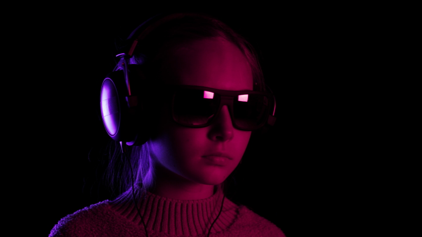 Teenager girl singing and dancing in headphones in dark studio with red and blue lighting. Young girl listening music and singing song on black background #1039930763