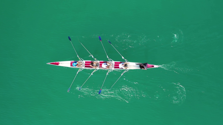 Aerial drone bird's eye view video of sport canoe operated by team of young women in emerald lake waters