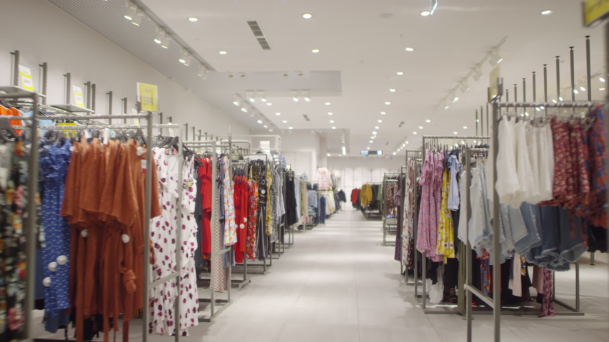 Dollying shot of camera moving through aisle in fashion store and passing by racks of carefully arranged brightly colored clothing prepared for opening | Shutterstock HD Video #1039943990