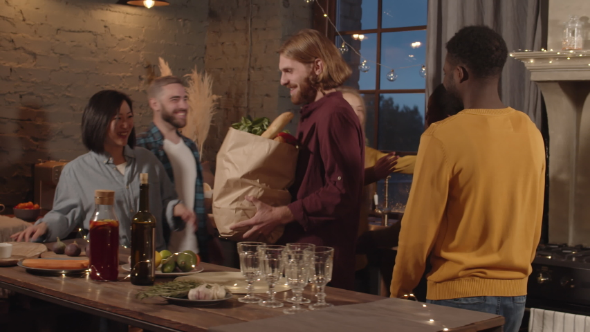 Tracking shot of happy people smiling and hugging guests arriving to dinner party in their apartment. They are chatting and thanking their friends for bringing groceries Royalty-Free Stock Footage #1039947302