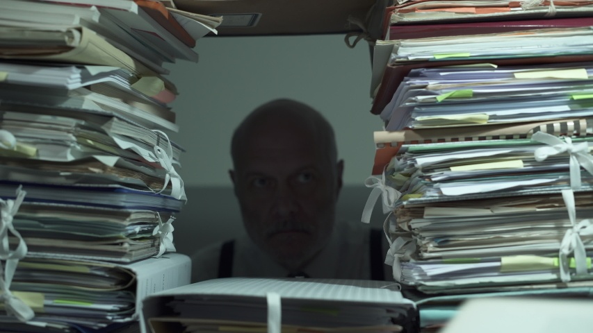 Office clerk working behind a wall of paperwork, he is peeking from a hole and taking a file, bureaucracy concept | Shutterstock HD Video #1039948394