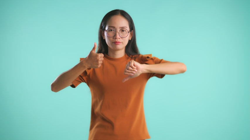 Confused young Asianwoman choosing between thumbs up and thumbs down