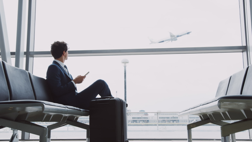 Businessman Sits In Airport Departure Lounge Using Mobile Phone With Plane Taking Off In Background