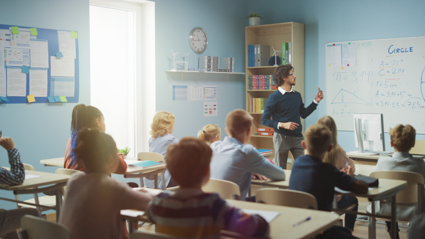 Caring Teacher Explains Lesson to a Classroom Full of Bright Diverse Children. In Elementary School with Group of Smart Multiethnic Kids Learning Science, Whole Classroom Raising Hands Knowing Answer | Shutterstock HD Video #1039966991