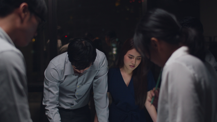 Millennial Asia businessmen and businesswomen meeting brainstorming ideas about new paperwork project colleagues working together planning success strategy enjoy teamwork in small modern night office. Royalty-Free Stock Footage #1039968614
