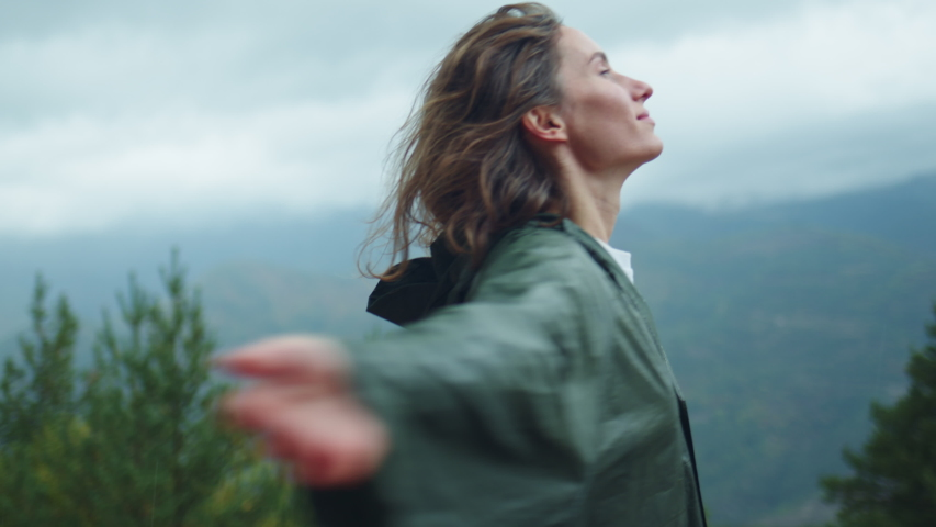 Female hiker with wet curly hair enjoying nature raising head up and looks in the sky feeling alive and free in nature breathing clean and fresh air at rainy day, Vacation Hiking in Pyrenees Mountains | Shutterstock HD Video #1039980713