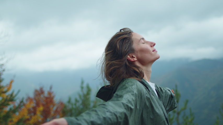 Free Happy Young Hiker Woman in green raincoat looking up with raised arms enjoying calm rainy day in the nature breathing fresh air, hair blowing in wind, People Mountains Freedom Concept, Happiness