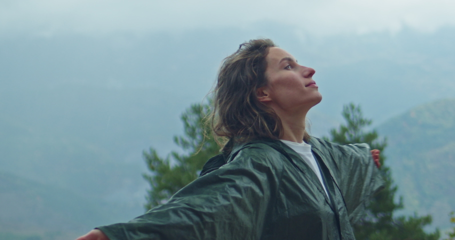 Happy hiker woman with wet curly hair dressed in green raincoat raising head up and looks at sky feels free breathing fresh and clean air in the mountains, autumn foggy landscape on the background | Shutterstock HD Video #1039980740