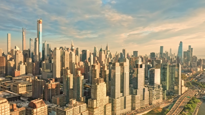 Aerial drone footage of New York skyline featuring Riverside skyscrapers and the Joe DiMaggio highway, next to the Hudson river, on a sunny late afternoon (with slow camera panning) | Shutterstock HD Video #1039995887