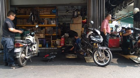 KUALA LUMPUR, October 10, 2019: Motorcycle technician repairing the motorcycle in garage.
