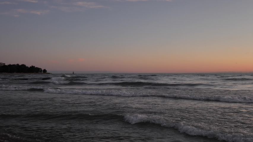 Clip of waves rolling into shore and crashing into one another and splashing in the distance early in the morning as the sky begins to turn pink with trees in the distance. | Shutterstock HD Video #1040003072
