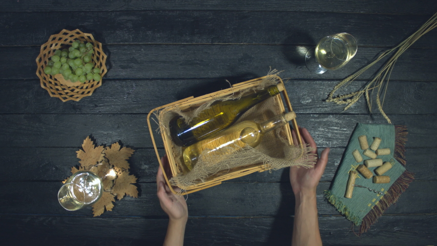 Bottles of expensive white wine on black background. Top View. In rich restaurant waiter puts basket with white wine bottles on table. Nearby are: full glasses with white wine, green grapes, wheat. | Shutterstock HD Video #1040015135