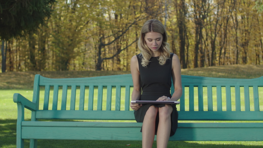 Businesswoman sitting in a park on a bench. Woman is opening laptop   Shutterstock HD Video #1040021156