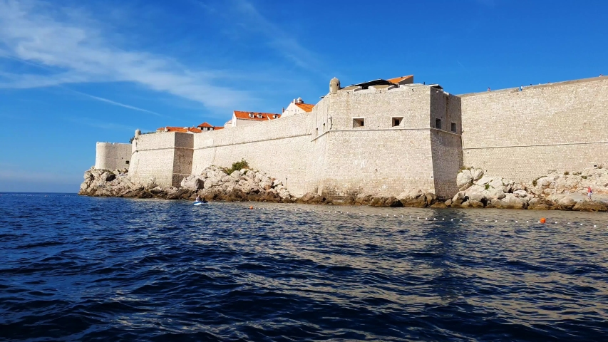 City medieval wall that surrounds the Dubrovnik Old Town view from a boat. Adriatic sea along the Croatian coastline.