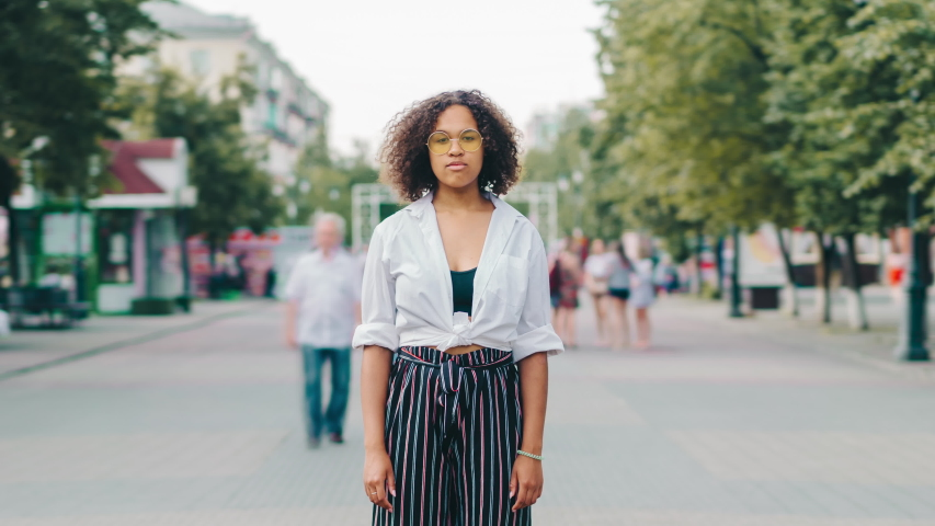 Zoom out time lapse portrait of African American lady in stylish clothing in pedestrian city street looking at camera with serious expression. Life and youth concept.
