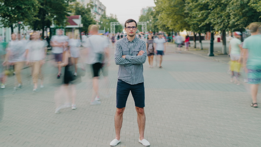 Time lapse of handsome young man wearing casual clothing standing in pedestrian street with hands crossed looking at camera with serious face on summer day. #1040030867