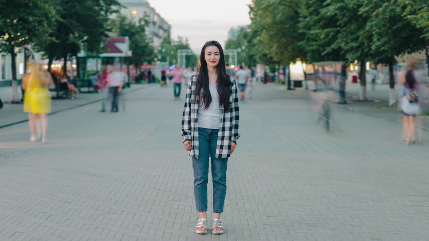 Time lapse of beautiful happy girl standing outdoors in city street smiling looking at camera wearing casual clothing. Youth, urban life and emotions concept. #1040030894
