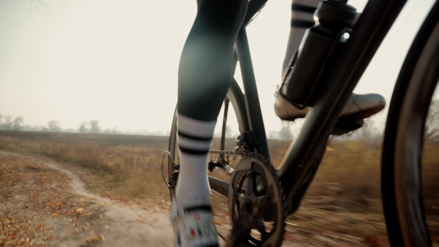 Cyclist Twists Pedals And Riding On Gravel Bike.Cycling Athlete At Fall Sunset On Park.Gear System Road Bicycle And Bike Wheel Rotation.Cyclist Twists Pedals And Riding On Road Bicycle.   Shutterstock HD Video #1040033390