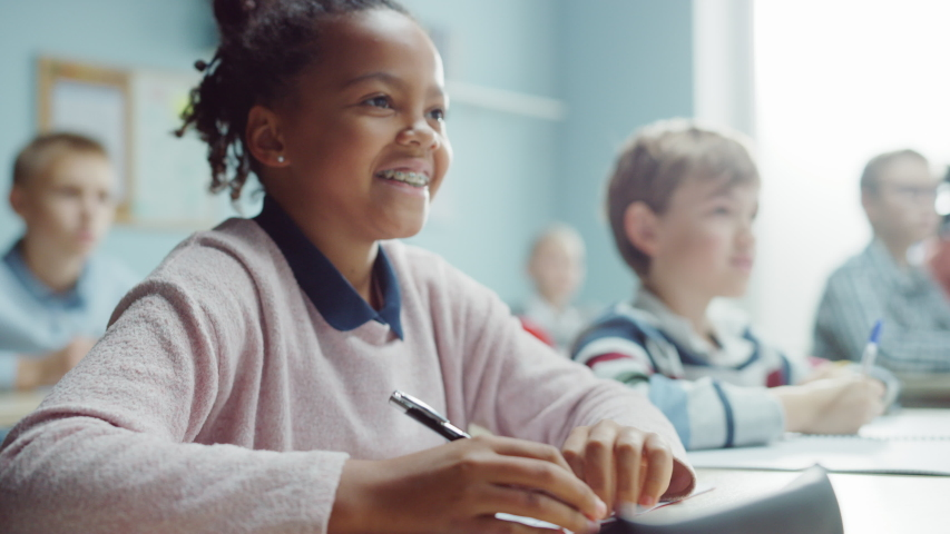 In Elementary School Class: Portrait of a Brilliant and Cute Black Girl with Braces Writes in Exercise Notebook, Smiles. Junior Classroom with Diverse Group of Bright Children Working Diligently