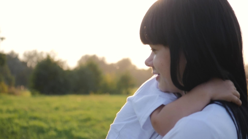A little blond girl hugs her mother's neck. A young mother holds her beloved child in her arms. Happy family walking in the fresh air at sunset.   Shutterstock HD Video #1040038721