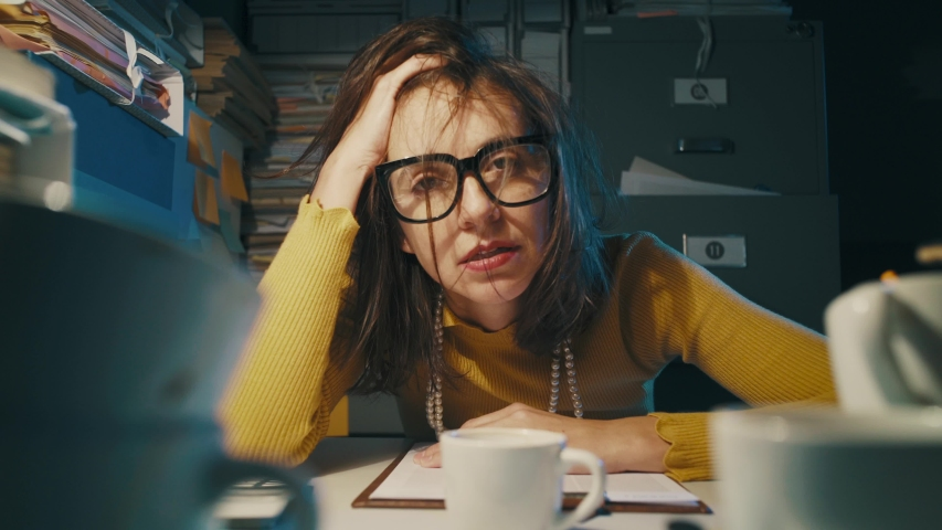 Stressed businesswoman working late at night in the office, she had too many cups of coffee and feels exhausted | Shutterstock HD Video #1040051333