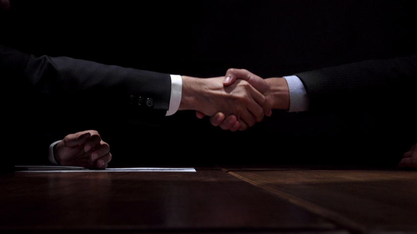 Anonymous business partners making handshake after confidential meeting in dark room  | Shutterstock HD Video #1040071598