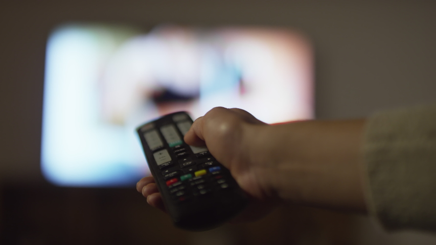 Close up shot of hands of unrecognizable woman holding remote control and changing channels on TV | Shutterstock HD Video #1040076713