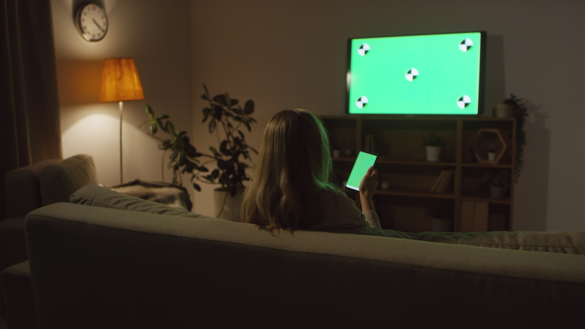 Rear view shot of unrecognizable woman sitting on couch in dark living room and using mobile phone with chromakey while watching TV #1040076860
