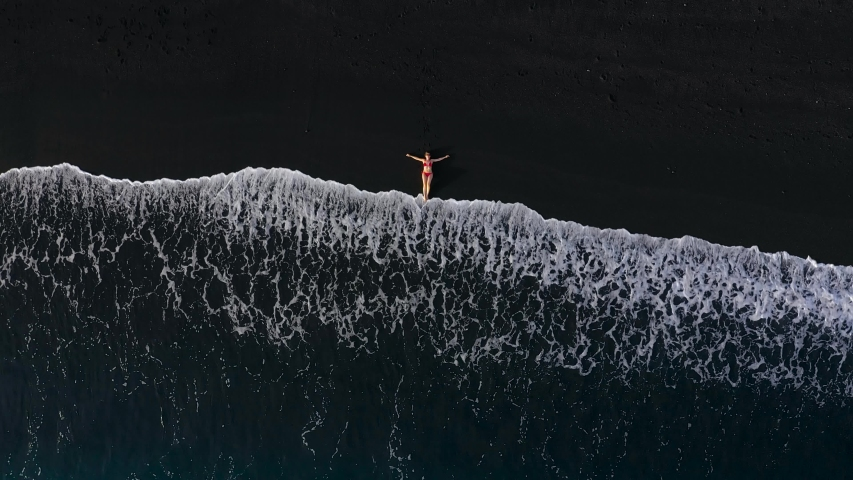 Top view of a woman in a red swimsuit lying on a black beach on the surf line. Coast of the island of Tenerife, Canary Islands, Spain.