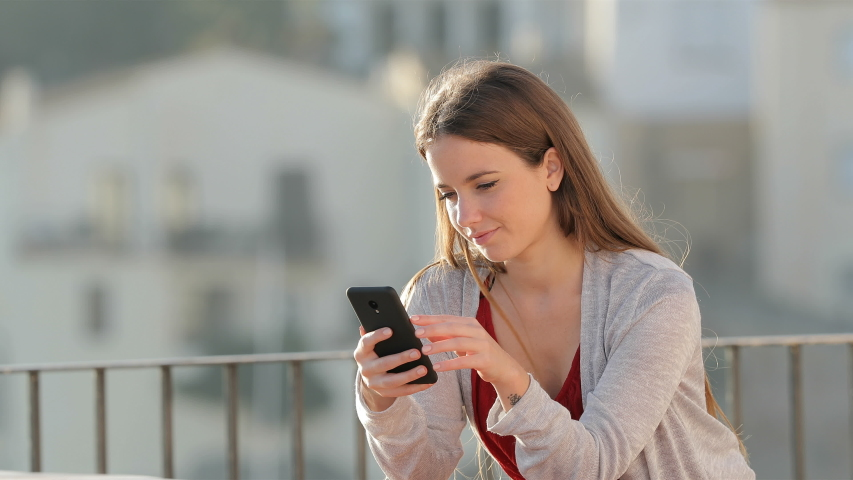 Excited woman checking mobile phone content celebrating success in a balcony a sunny day | Shutterstock HD Video #1040092364