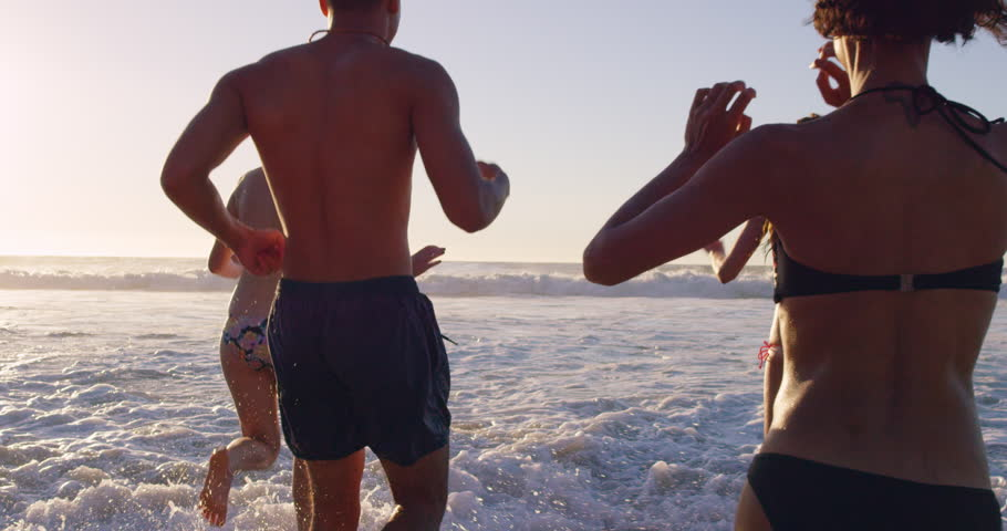 Group of friends swimming in the sea at sunset running into water getting wet and making splashes RED DRAGON #10400969