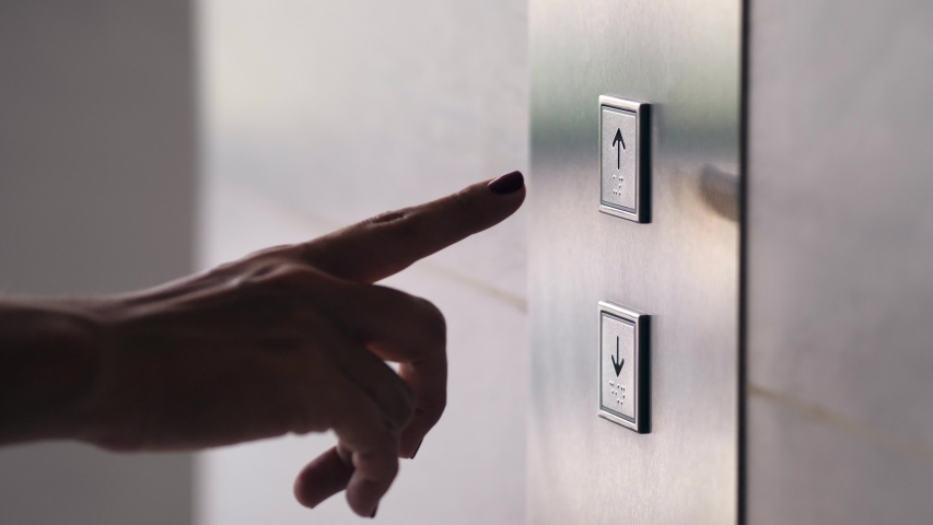 Female Hand Pushing Elevator Button in Office Center or Hotel. Young Woman Pressing Lift Button Up. 4K Slowmotion.