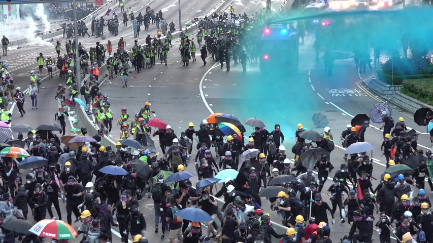 HONG KONG – 15 SEPTEMBER 2019: Crowds of protesters wearing black clothes, protective helmets and gas masks run from police, as special forces move in with water cannon and tear gas